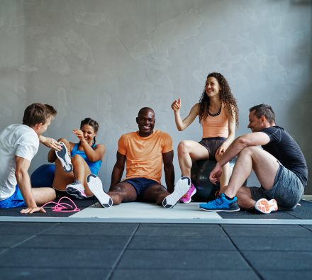 Group of young friends in sportswear talking and laughing while sitting together on the floor of a gym after a workout